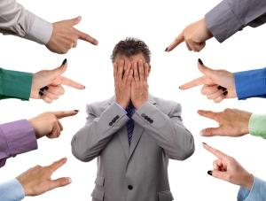Hands pointing towards businessman holding head in hands concept